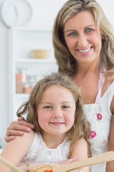 Moeder die dochter koestert en salade maakt