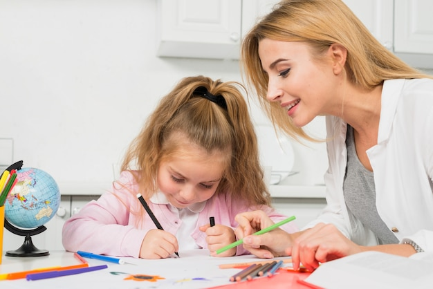 Moeder die dochter met haar thuiswerk helpt