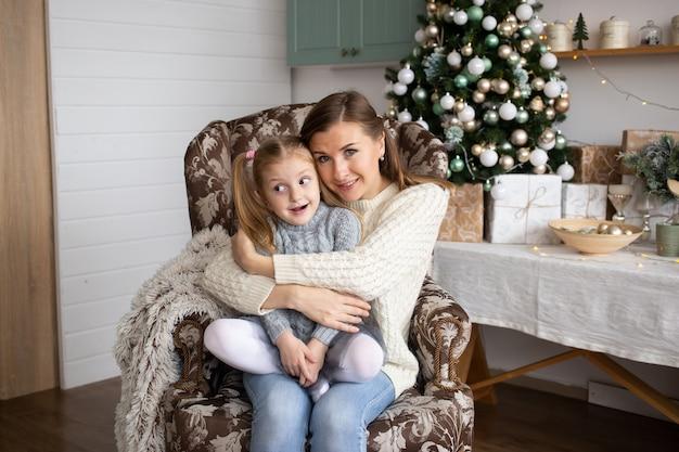 Moeder die dochter op de achtergrond van het kerstmishuis koestert