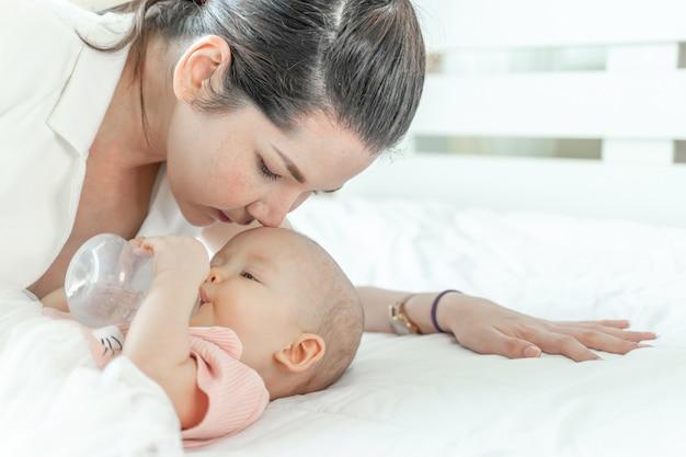 Moeder die een baby kust die uit een fles drinkt