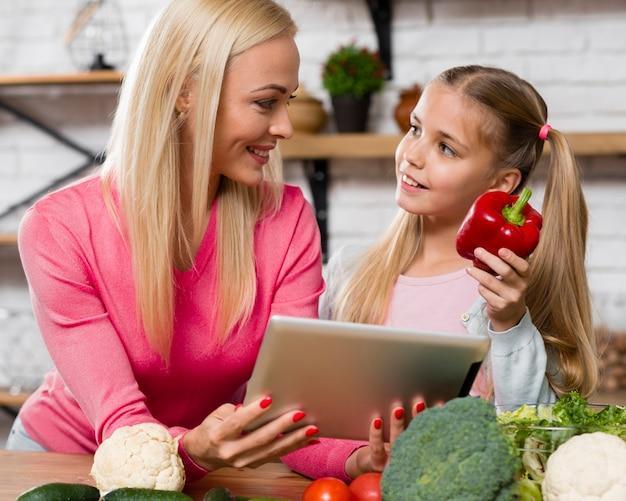 Moeder die een digitale tablet en een dochter houdt die paprika houdt