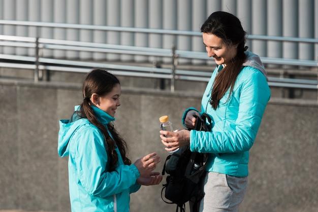 Moeder die een fles water geeft aan haar dochter