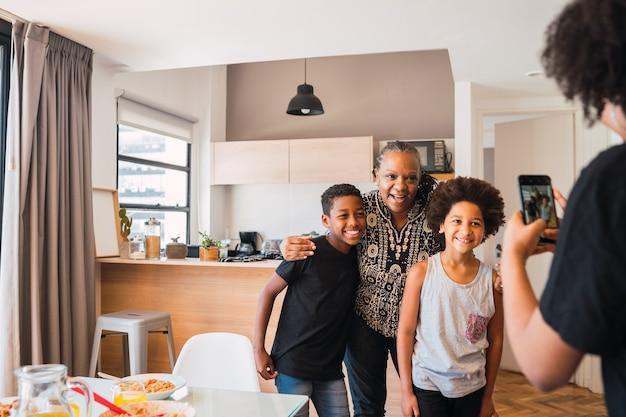 Moeder die een foto maakt van oma met haar kleinkinderen thuis