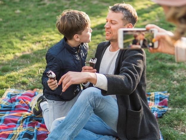 Moeder die een foto van vader en zoon neemt
