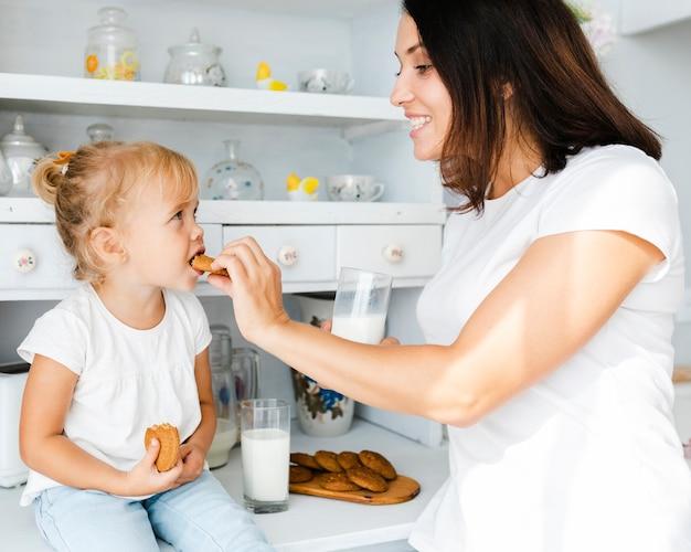 Moeder die een koekje geeft aan haar dochter