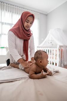 Moeder die een massage van de babyjongen geeft