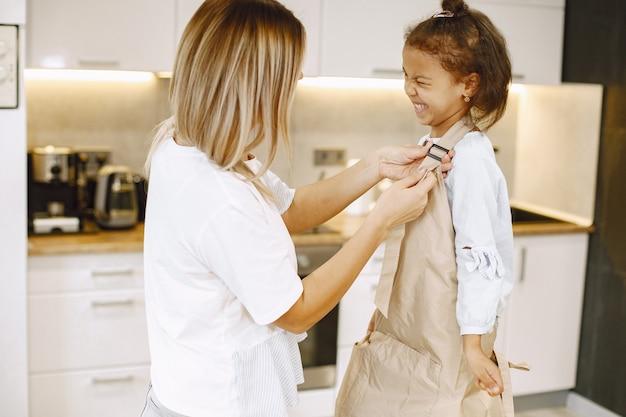 Moeder die een schort geeft aan haar dochter. zorgzame gelukkige moeder die samen kookt met een klein etnisch kind