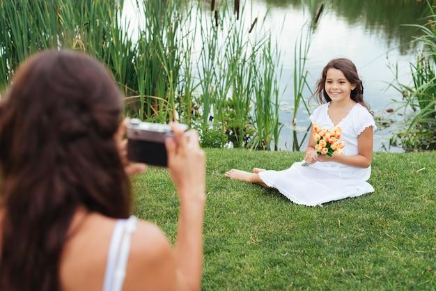 Moeder die foto van dochter neemt door het meer
