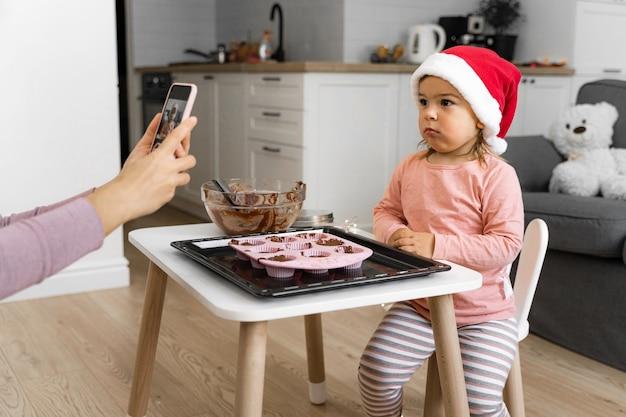 Moeder die foto van kind thuis neemt. modern moederschap
