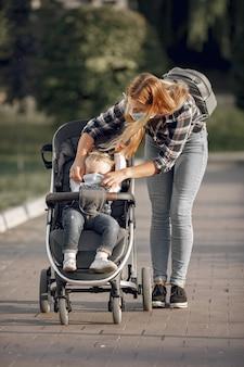 Moeder die gezichtsmasker draagt. moeder met baby kinderwagen tijdens pandemie buiten wandelen.