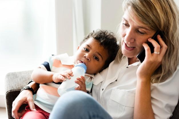 Moeder die haar baby voedt terwijl op de telefoon