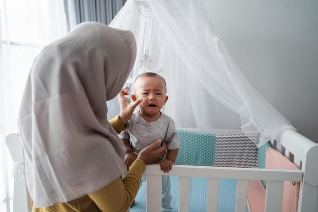 Moeder die haar babyjongen bekijkt die huilt