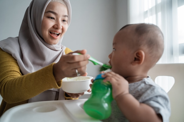 Moeder die haar babyjongen voedt terwijl het zitten op hoge stoel