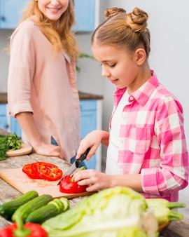 Moeder die haar dochter bekijkt die de rode groene paprika met mes op houten lijst snijdt