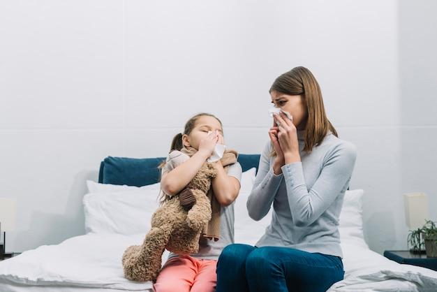 Moeder die haar dochter bekijkt die haar neus met papieren zakdoekje blaast