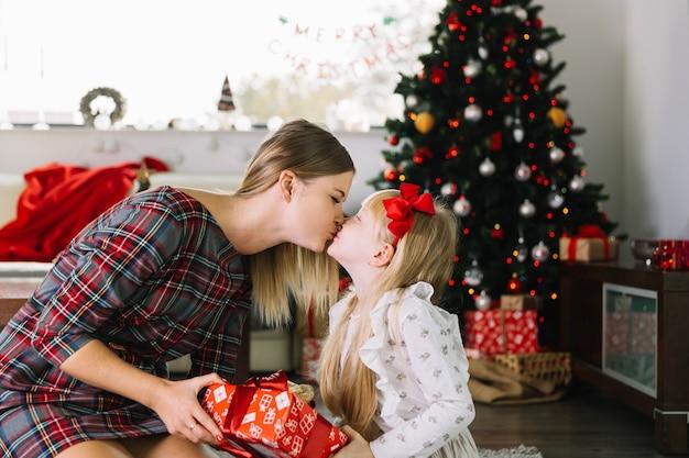Moeder die haar dochter kust bij kerstmis