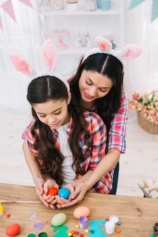 Moeder die haar dochter omhelst die rode en blauwe eieren op pasen-dag houdt