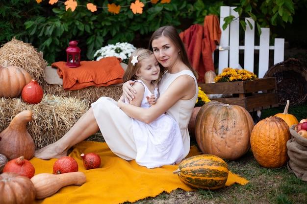 Moeder die haar dochter op de herfstachtergrond koestert met pompoenen