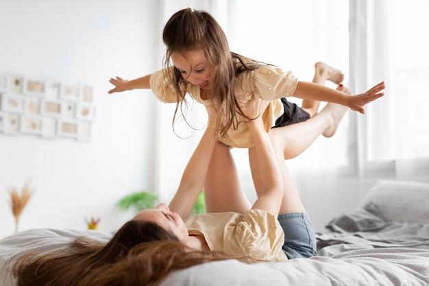 Moeder die haar dochter op haar benen houdt