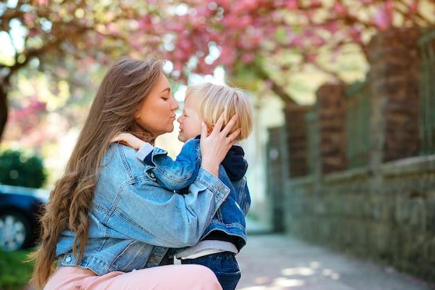 Moeder die haar droevig kind in openlucht kalmeert. moeder met boos baby op een wandeling in het voorjaar straat.