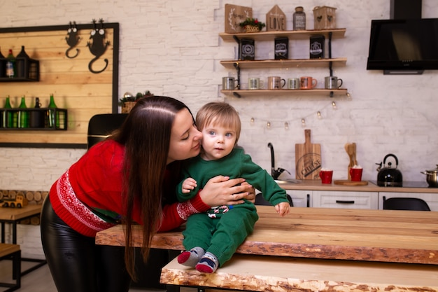 Moeder die haar kind in keuken thuis kust.