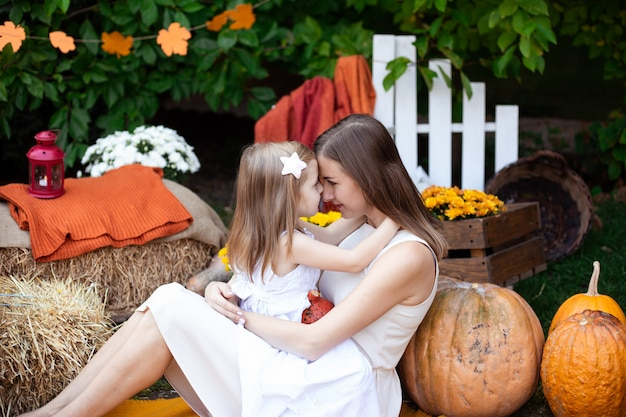 Moeder die haar kind op de herfstachtergrond kust