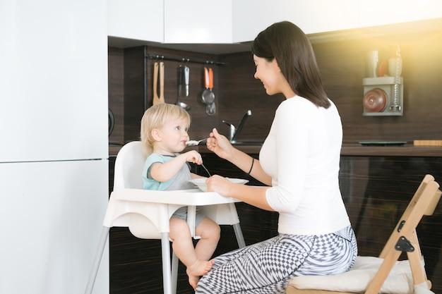 Moeder die haar kind voedt. eerste vast voedsel voor een jaar oud kind. babysitting op kinderstoel of verhuur. moeder en kleine jongen eten pap. gezonde voeding voor kinderen. bovenliggende feed kind op keuken.