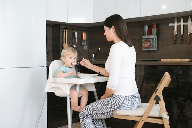 Moeder die haar kind voedt. eerste vast voedsel voor een jaar oud kind. babysitting op kinderstoel of verhuur. moeder en kleine jongen eten pap. gezonde voeding voor kinderen. ouders voeden kinderen op keuken.