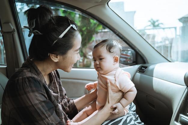 Moeder die haar kleine baby in de auto