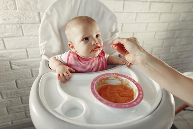 Moeder die haar kleine baby in een keuken voedt