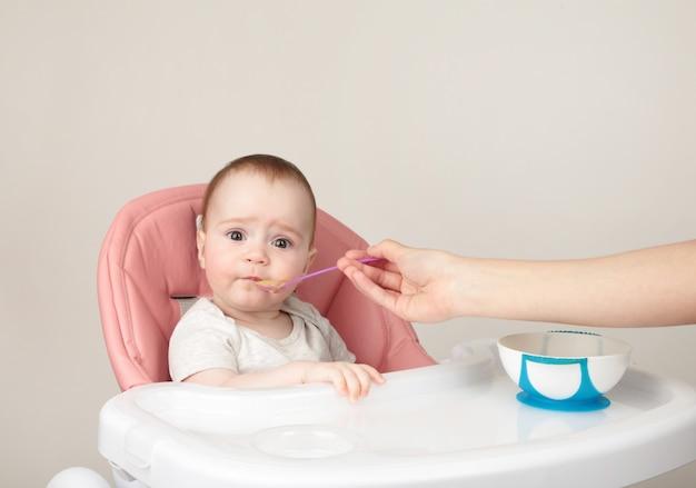 Moeder die haar leuk babymeisje als voorzitter op grijs voedt.