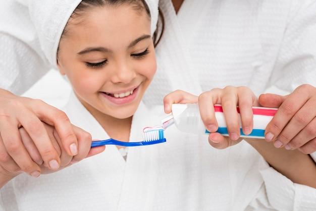 Moeder die haar meisje helpt om haar tandenclose-up te borstelen