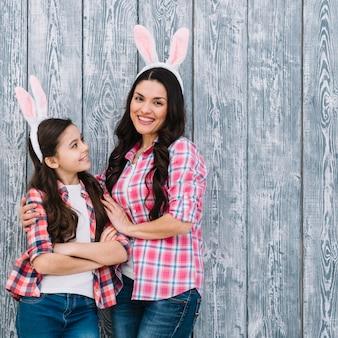 Moeder die haar mooie dochter omhelst die konijntjeoren op grijze houten muur draagt