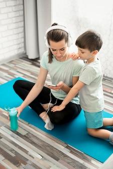 Moeder die haar oefeningen van de zoonssport toont