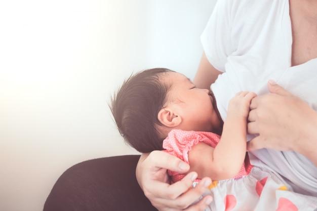 Moeder die haar pasgeboren babymeisje de borst geeft.