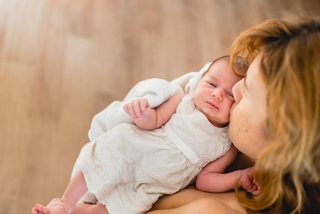 Moeder die haar pasgeboren dochter na het de borst geven kust