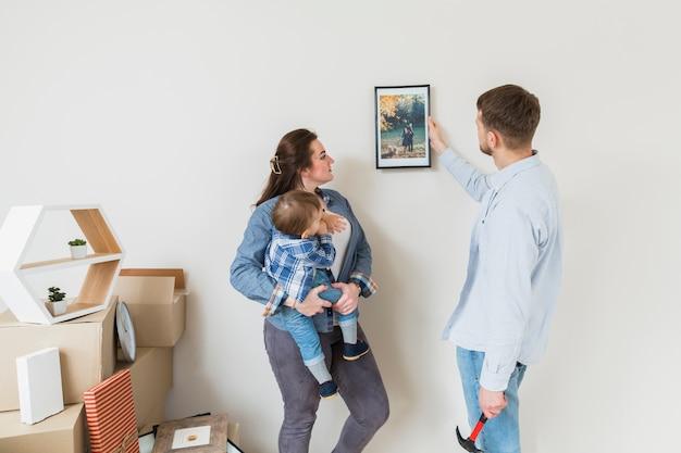 Moeder die haar zoon draagt die frame bekijkt dat door zijn echtgenoot op muur wordt vastgemaakt
