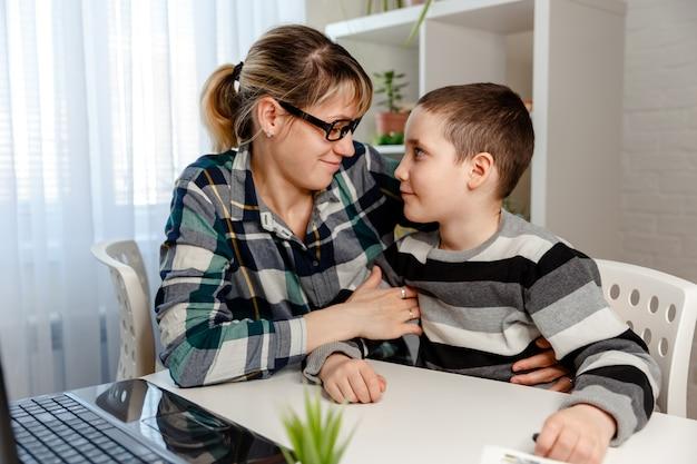 Moeder die haar zoon helpt die schoolthuiswerk thuis maakt. thuisonderwijs