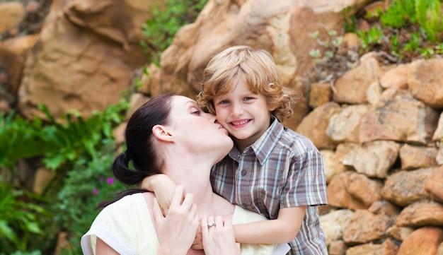 Moeder die haar zoon in een park kust