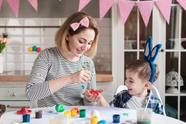 Moeder die haar zoon onderwijst hoe te om eieren voor pasen te schilderen