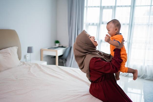Moeder die haar zoon op schoot tijdens het spelen zittend op het bed