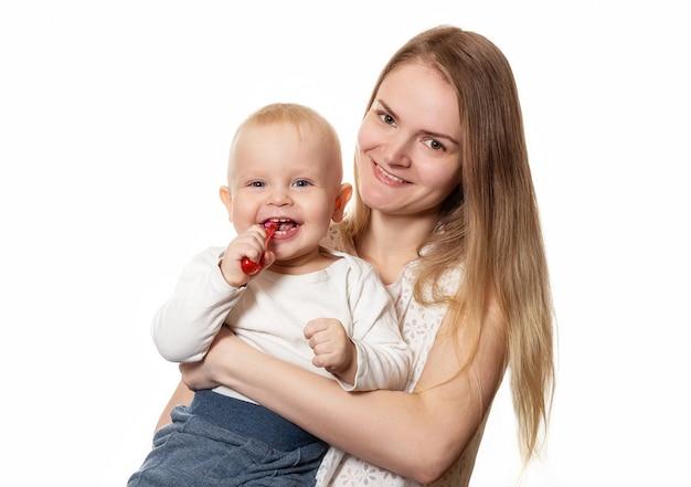 Moeder die het borstelen van de baby tanden onderwijst. jongen zijn tanden poetsen met een tandenborstel voor baby.
