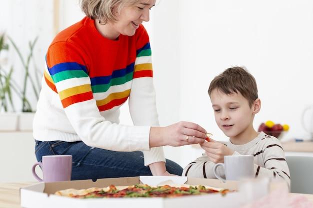 Moeder die het desinfecterende middel van de kindhand geeft alvorens pizza te eten