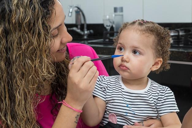 Moeder, die het gezicht van het kind op haar schoot schildert.