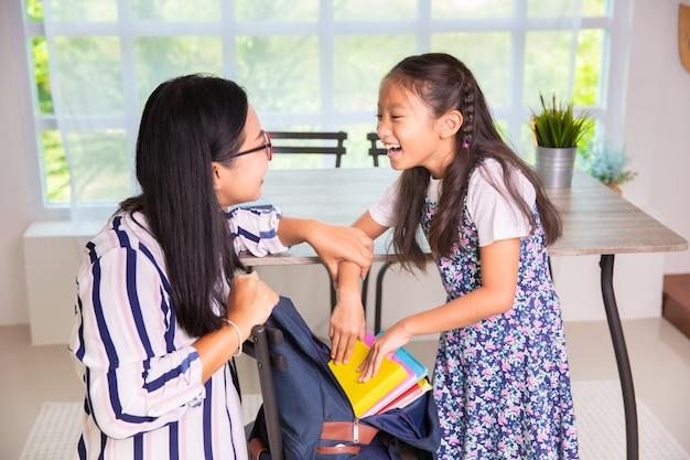Moeder die het meisje van de basisschool helpt boeken inpakken aan de zakken