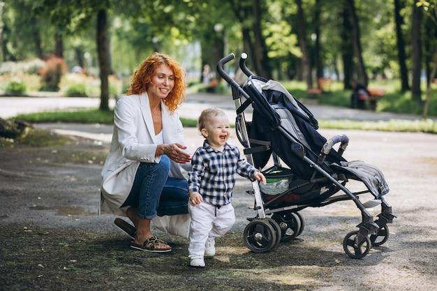 Moeder die in park met haar kleine zoon loopt