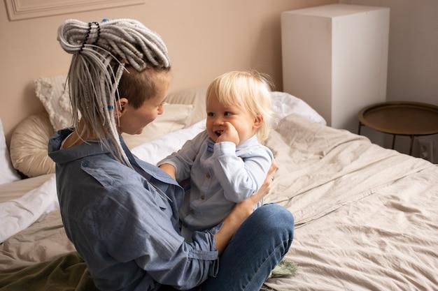 Moeder die jongenszoon thuis op bed kijkt. gelukkige familie plezier thuis