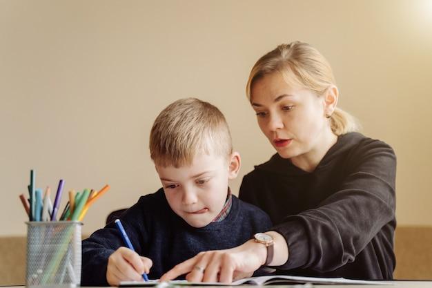 Moeder die laptop en tablet het onderwijs met haar zoon thuis online in zijn ruimte gebruiken