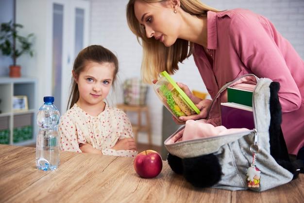 Moeder die lunchdoos met gezond voedsel in de rugzak van de dochter stopt