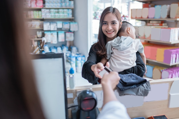 Moeder die met creditcard betaalt in de babywinkel